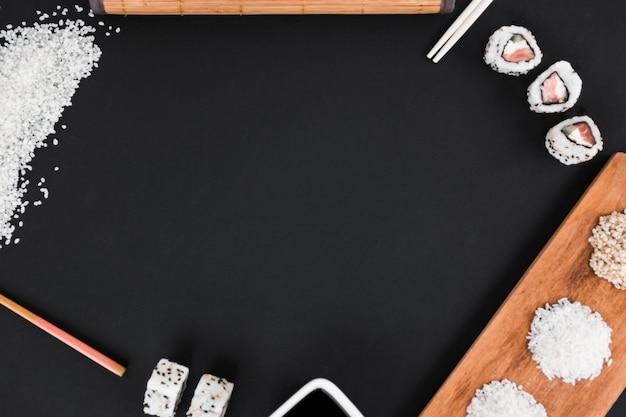 Riz pas cuit; baguettes; sushi et sauce soja sur fond noir