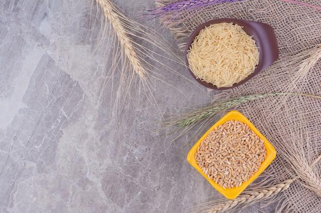 Riz et pâtes préparés à partir de celui-ci dans des assiettes séparées