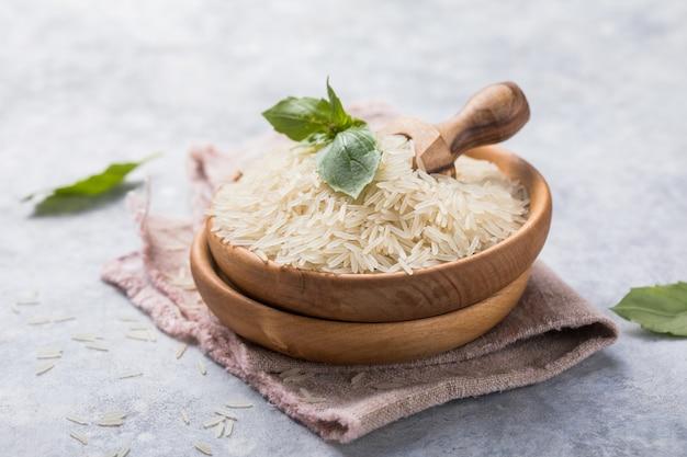 Riz poli blanc dans un bol en bois. fond de riz à grain long.