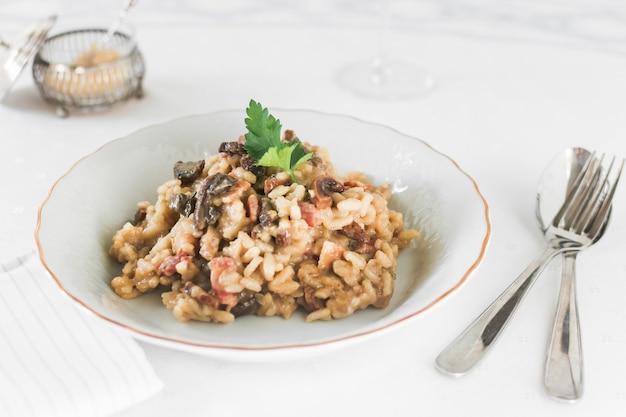 Riz risotto aux champignons sur plaque en céramique blanche