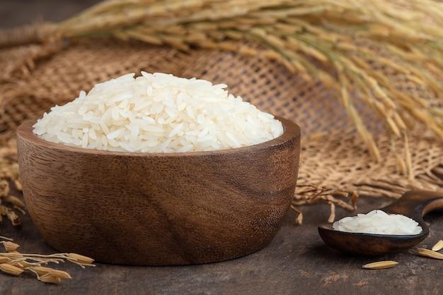 Riz.riz blanc (riz au jasmin thaïlandais) dans un bol en bois sur fond de bois.riz au jasmin dans un bol et sac de jute sur table en bois
