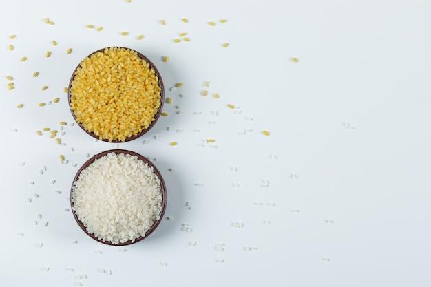 Riz rond cru avec un bol de boulgour sec dans un bol en argile sur fond blanc, à plat.