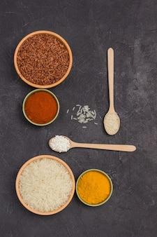 Riz rouge et blanc dans des bols. curcuma et poivron rouge moulu. riz blanc dans une cuillère en bois. surface noire. mise à plat