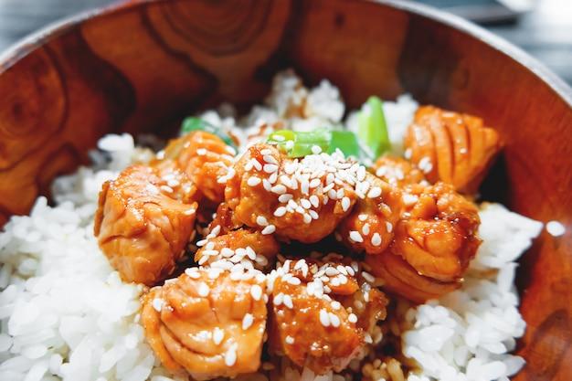 Riz en sauce avec légumes sautés et saumon dans un bol en bois