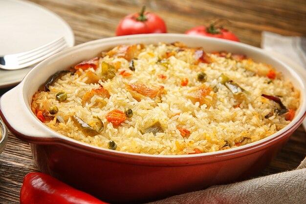Riz savoureux avec du poulet et des légumes dans un plat allant au four sur la table de la cuisine