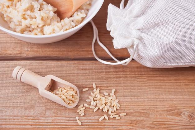 Riz sec et cuillère en bois sur bois