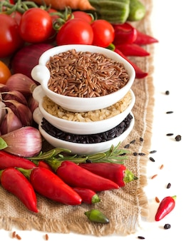 Riz sec rouge, noir et non poli cru cru dans des bols avec des légumes sur une toile de jute isoler sur blanc close up