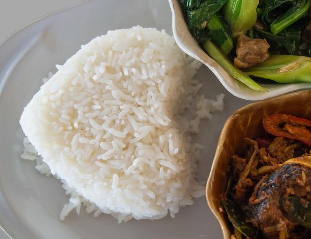 Riz avec stir fried fish et stir fried vegetables dans le bol sur la plaque blanche