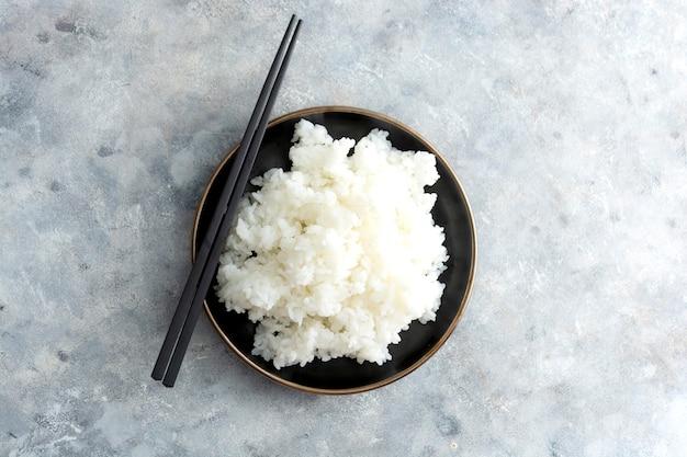 Riz sushy avec des baguettes vue de dessus isolée, ingrédient pour la cuisson des sushis traditionnels