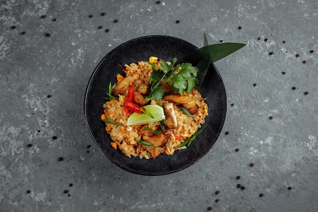 Riz thaï au poulet. plat thaï de riz, poulet, oignon yalta, maïs, ananas, tomate, sauce soja, pâte de chili, coriandre, citron vert, piment
