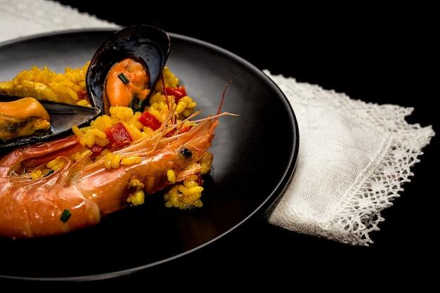 Riz traditionnel en paella avec du poisson et de la viande.