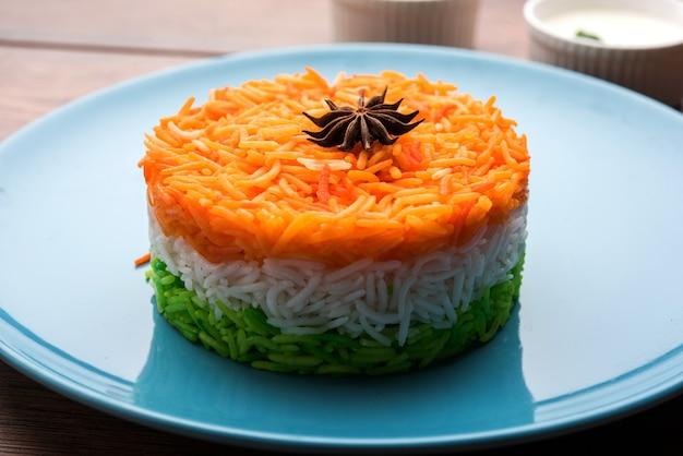 Riz tricolore tiranga pour la république indienne et le jour de l'indépendance, servi dans une assiette en céramique, mise au point sélective