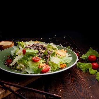 Riz versant sur un délicieux repas de salade dans une assiette avec des baguettes sur une vue de côté en bois et fond noir. espace pour le texte