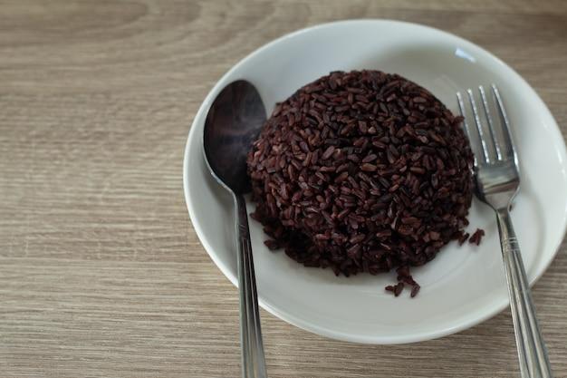 Riz violet cuit sur un plat blanc prêt à servir