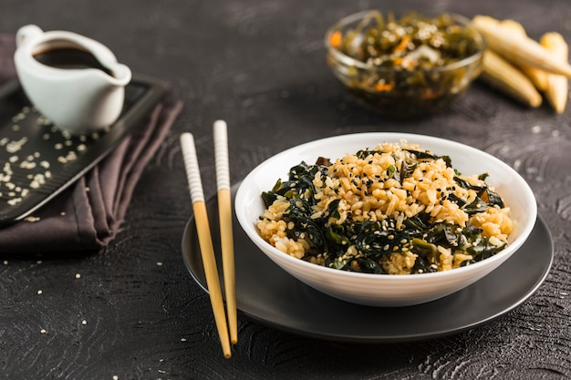 Riz wok aux algues dans une assiette blanche avec des baguettes et de la sauce soja.