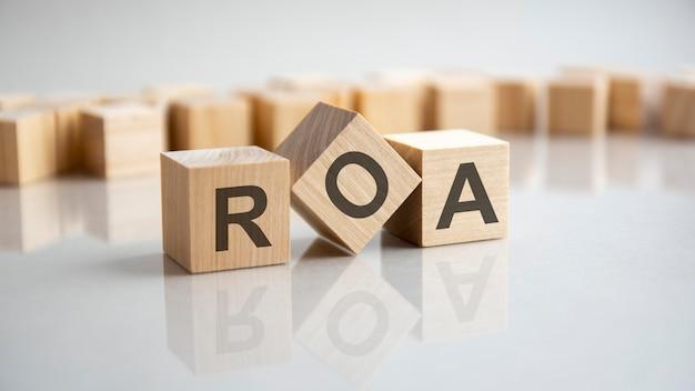 Roa - concept d'acronyme de retour sur actifs sur cubes, fond gris. réflexion sur la surface réfléchissante de la table. mise au point sélective.