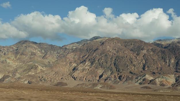 Road trip à death valley, artists palette drive, california usa. auto-stop voyageant en amérique. autoroute, montagnes nues colorées et nature sauvage au climat aride. vue depuis la voiture. voyage au nevada.
