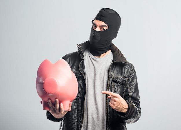 Robber tenant une tirelire