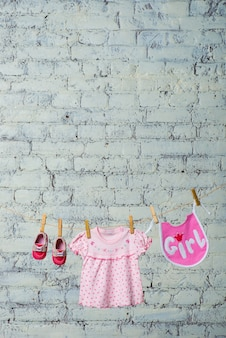 Robe bavoir pour enfants et chaussures rouges pour la fille sèchent sur une corde sur un mur de briques blanches