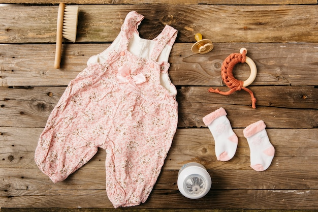 Robe de bébé; brosse; sucette; jouet et paire de chaussettes avec une bouteille de lait sur une table en bois