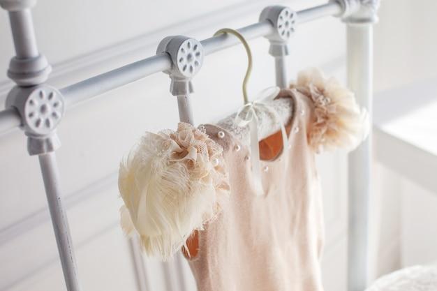 Robe beige en laine et détails ajourés. sute fait à la main pour bébé fille pèse sur un cintre