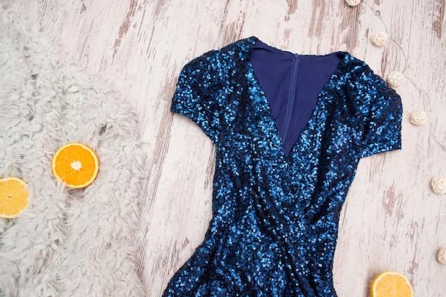 Robe bleue en paillettes et oranges sur une fausse fourrure grise, fond bois.