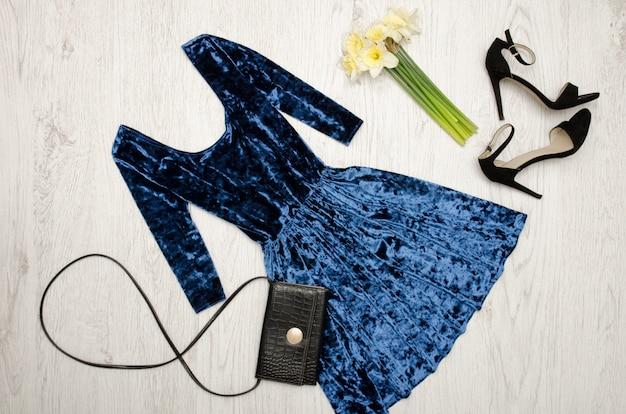 Robe bleue velours, chaussures noires, pochette et un bouquet de jonquilles