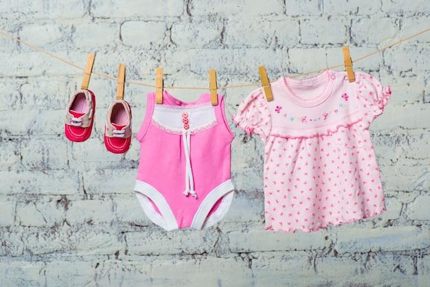 Robe corsage rose pour enfants et chaussures rouges pour la fille sèche sur une corde contre un mur de briques blanches