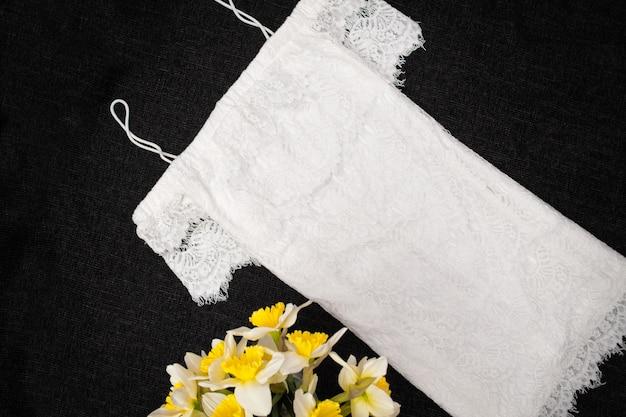 Robe en dentelle blanche et bouquet de jonquilles.
