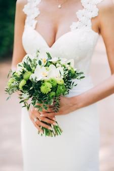 Robe à encolure profonde. mariée tient un bouquet de mariée. bouquet de mariée avec des verts. forme féminine. jolie fille avec un bouquet de fleurs