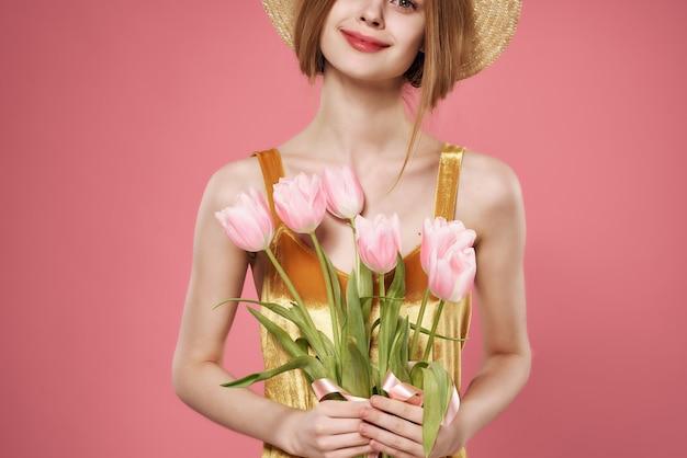 Robe femme dorée avec bouquet de fleurs décoration fond rose luxe