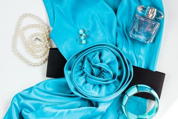 Robe de femme turquoise vif et accessoires sur fond blanc