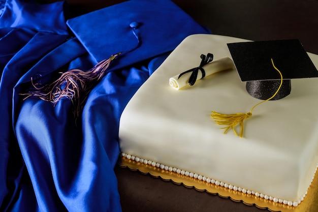 Robe de graduation bleue et casquette avec gâteau pour la fin de l'école.