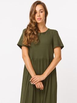 Robe longue informe olive, manches longues, chaussures hautes noires. corps mince, peau de soie. sourire blanc, visage doux, coiffure brune.