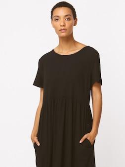 Robe longue noire informe, manches longues, chaussures hautes noires. corps mince, peau de soie. sourire blanc, visage doux, coiffure brune.