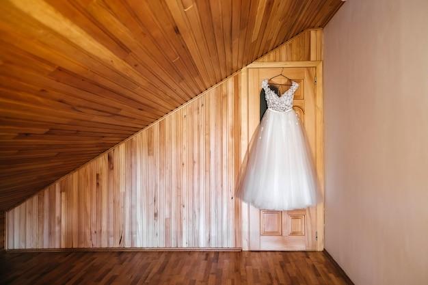 Robe de mariée accrochée à la porte sur fond de mur en bois