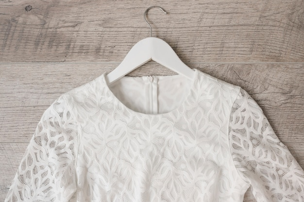 Robe de mariée blanche sur cintre contre un fond texturé en bois