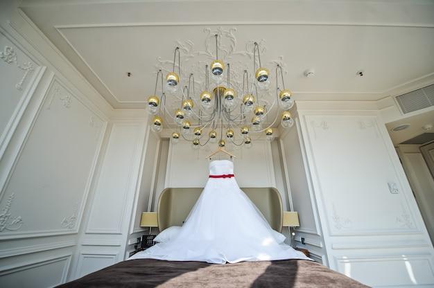 Robe de mariée blanche de la mariée suspendue au lustre de la chambre d'hôtel