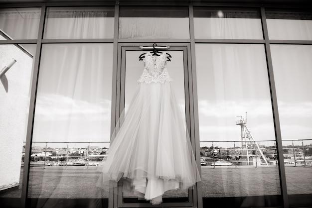 Robe de mariée blanche suspendue dans la chambre. robe de mariée blanche