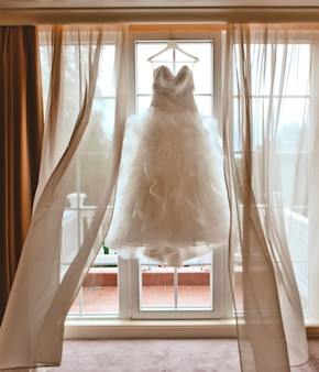 Robe de mariée blanche suspendue près de la fenêtre avec des rideaux