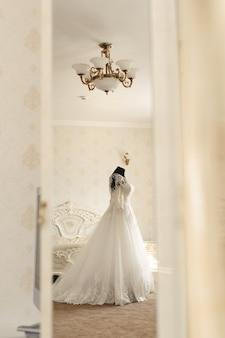 Robe de mariée chic et voile sur mannequin dans la salle de réunion de la mariée. vue à travers la porte.