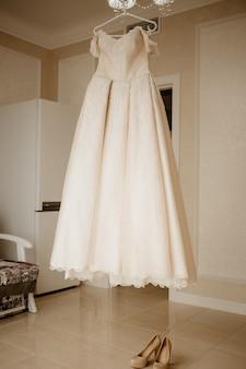 Robe de mariée sur cintre et chaussures sur le sol dans la salle de la mariée