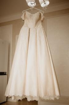 Robe de mariée sur cintre dans la chambre de la mariée