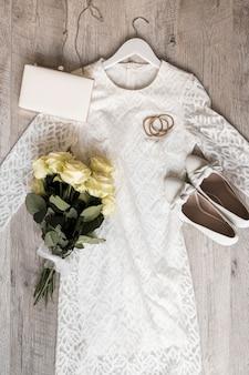 Robe de mariée avec embrayage de chaussures; bandeaux pour les cheveux et bouquet de roses attachées avec un ruban blanc sur fond en bois