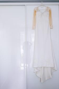 Robe de mariée sur le fond blanc de la fenêtre