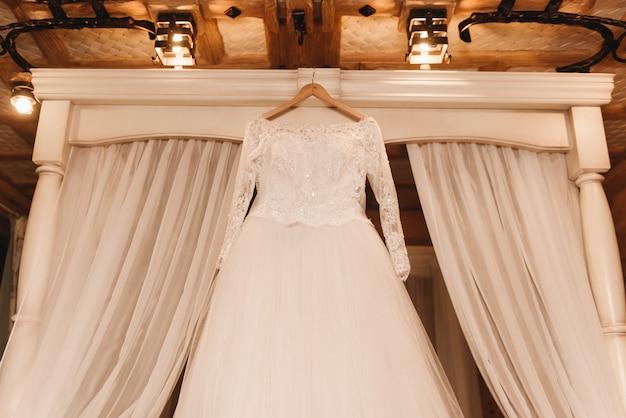La robe de mariée de la mariée est suspendue sur un lit en bois blanc