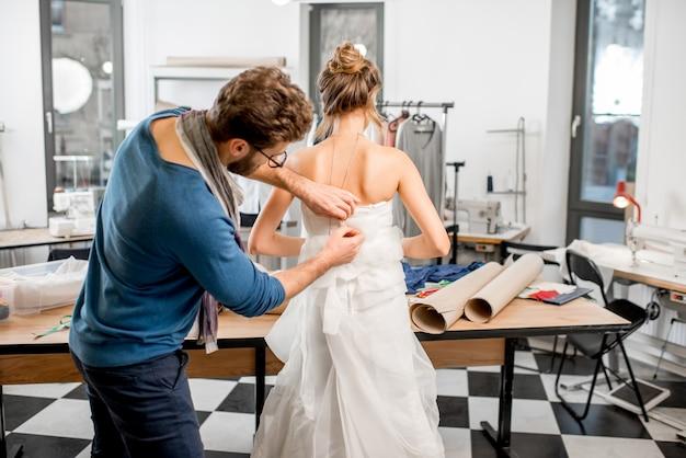Robe de mariée de montage client jeune femme avec tailleur homme debout au studio de couture