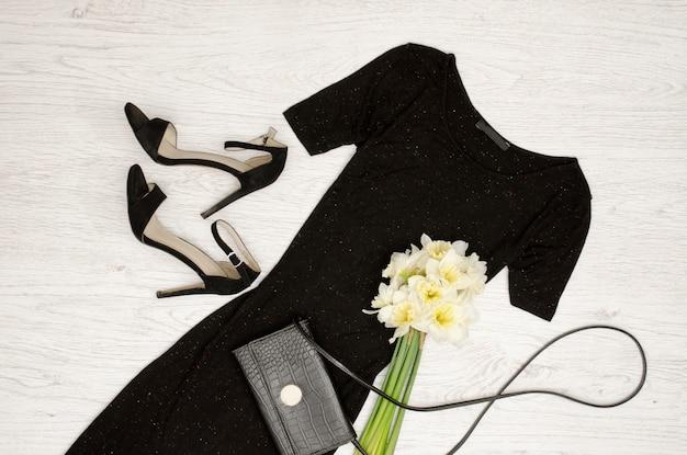 Robe noire, chaussures, pochette et un bouquet de jonquilles