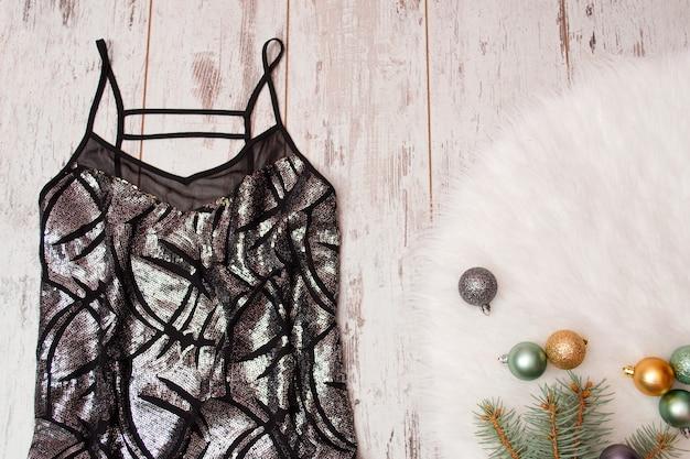 Robe noire en feu sur fond de bois, boules de noël sur fourrure blanche. concept à la mode, vue de dessus