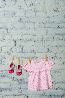 Robe rose bébé et chaussures rouges pour la fille, sèches sur une corde contre un mur de briques blanches.